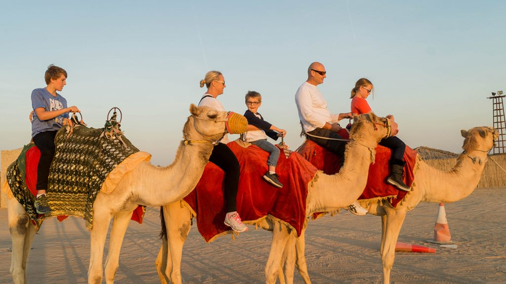 Family riding camels in Dubai