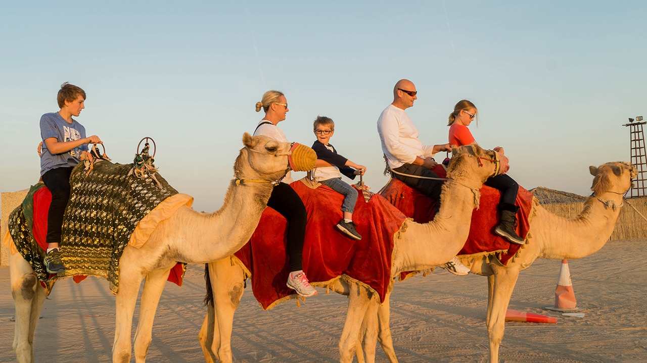Camel riding and sand dune surfing in dubai my desert safari family riding camels in dubai altavistaventures Choice Image
