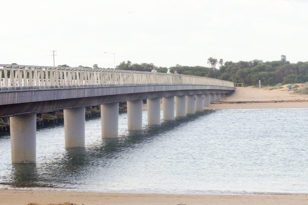 A overexposed image of a concrete bridge crossing between two beaches